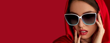 gorgeous brunette woman with luxurious make-up in white sunglasses and red headscarf on red background. copy space for text Фото со стока