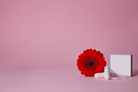 menstrual sanitary cotton tampons, box for tampons and red flower on pink background. copy space. Feminine hygiene products