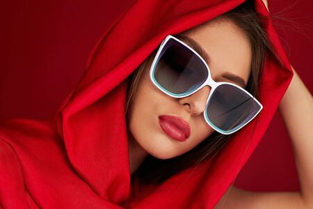 Portrait of beautiful brunette sexy girl with luxurious make-up in white sunglasses and red headscarf on red background Banque d'images - 149576674