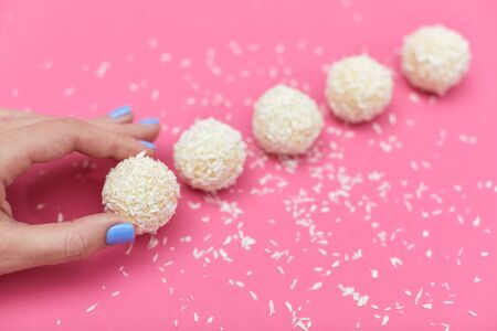 female hand with candies covered by shredded coconut. coconut balls on pink background Standard-Bild