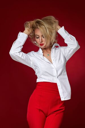gorgeous sexy blonde woman in white shirt and red pants on red background. Banque d'images - 149576683