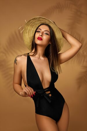 Sexy fashionable young woman in black swimsuit and hat posing on studio background. Banque d'images - 149576917
