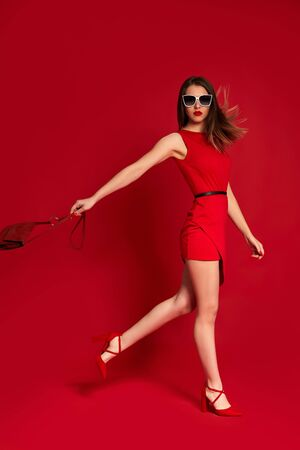 gorgeous fashionable woman holding red bag. brunette girl in luxurious sunglasses and red dress on red background. fashion concept Stok Fotoğraf