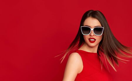gorgeous brunette woman with flying hair and luxurious make-up in white sunglasses on red background. copy space Banque d'images - 149576931