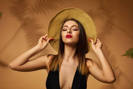 beautiful elegant fashionable young woman in black swimsuit and hat posing on studio background. Banque d'images - 149576938