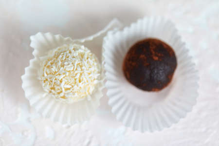 Candies covered by shredded coconut. coconut balls with coconut flakes. top view