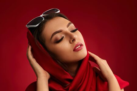 Portrait of beautiful brunette girl with luxurious make-up in bright red headscarf on red background
