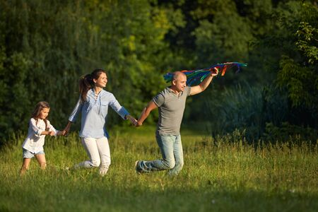 happy family with child girl launches kite in sunny day. family time Archivio Fotografico