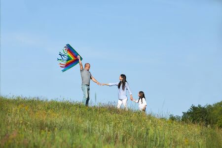 happy family with child girl launches kite in summer nature Archivio Fotografico