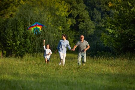 happy family with child girl launches kite in park in sunny summer day.