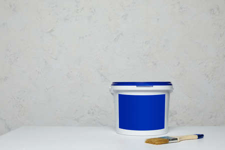 Closed blank blue can of paint and brush on table. Mockup for design. space for text