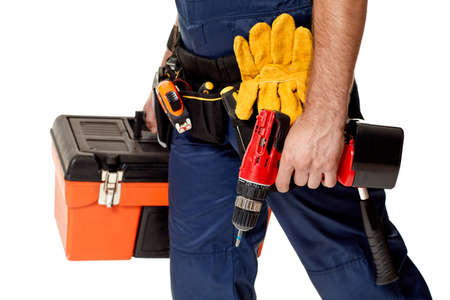 repairman holding cordless screwdriver and tool box. handyman with working tools on belt