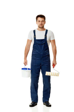 caucasian repairman in blue overalls holding paint roller and can with paint. builder or painter decorator isolated on white background