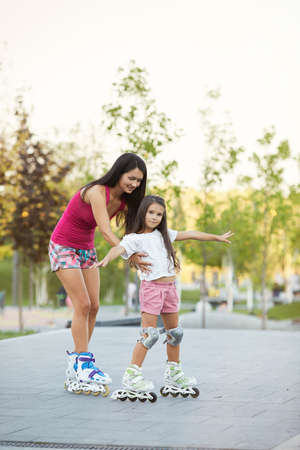 happy mother is teaching her little daughter to ride roller skates in summer park Banco de Imagens - 155443338