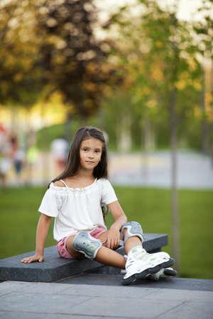 happy little child girl in roller skates is sitting in summer park.
