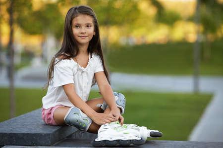smiling little child girl in roller skates is sitting in summer park.