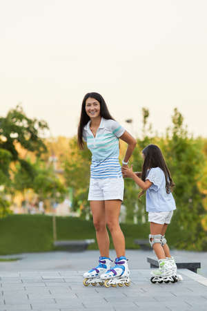 Young mother and her little daughter rollerskating in summer park. happy family have fun Banco de Imagens - 155443341
