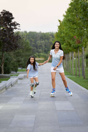 attractive mother and her cute little daughter rollerskating in summer park. happy family Banco de Imagens - 155502064