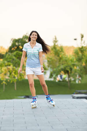 smiling young woman is rollerskating in summer park. Banco de Imagens - 155657177