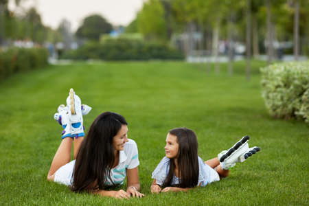 mother and daughter in roller skates are sitting on grass and having fun in park.
