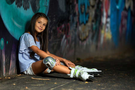 happy tired little child girl in roller skates is sitting after rollerskating in park in the evening Banco de Imagens - 155657178