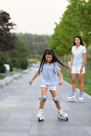 pretty mother and her little daughter rollerskating in summer park. happy family