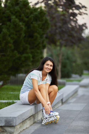 happy woman is wearing roller skates while sitting in summer park. Banco de Imagens - 155657179
