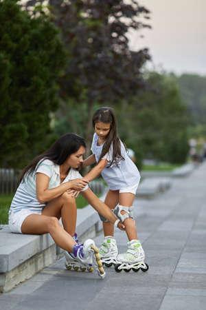 mother helps her little child daughter wearing roller skates in summer park. Banco de Imagens
