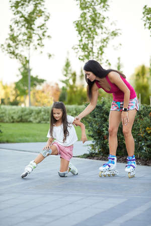 little child girl falled down while rolling with her mother in park. mom helps daughter get up after falling Banco de Imagens