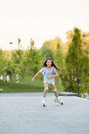 smiling cute little child girl rollerskating in summer park. Banco de Imagens - 155657180
