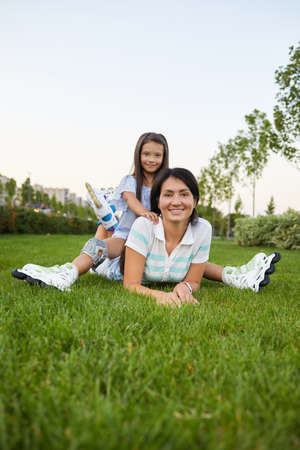 young mother and daughter in roller skates are sitting on grass in park. Banco de Imagens - 155558077