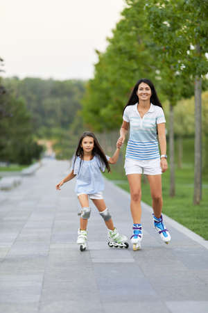 Young mother and her little daughter rollerskating in summer park. happy family have fun