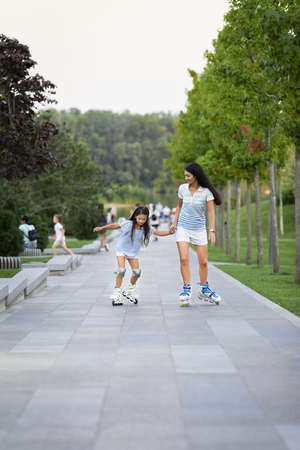 Young mother and her little daughter rollerskating in summer park. happy family have fun Banco de Imagens - 155558068