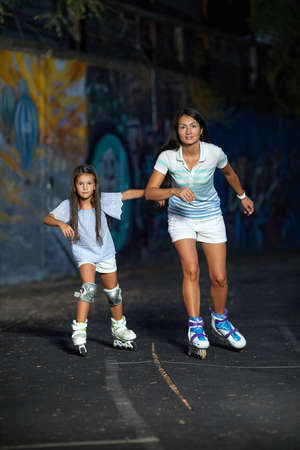 young mother and her little daughter rollerskating in the evening. family have fun Banco de Imagens - 155558040