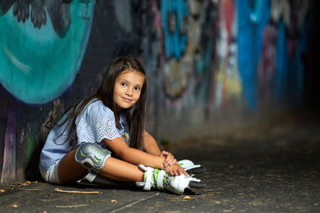 tired happy little child girl in roller skates is resting after rollerskating in park in the evening Banco de Imagens - 155657181