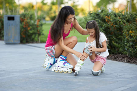 little child girl falled down while rolling with her mother in park. mom helps daughter get up after falling Banco de Imagens - 155486164