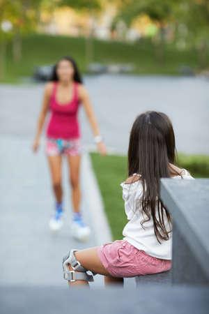 little child girl is waiting her mother in roller skates in summer park. Banco de Imagens - 155485158