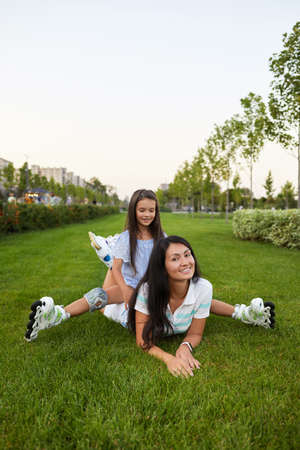 young mother and daughter in roller skates are sitting on grass and having fun in park. happy family outdoor Banco de Imagens - 155486218