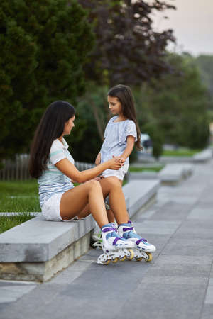 happy little child girl and her mother are wearing roller skates while sitting in summer park. Banco de Imagens - 155486111