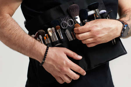 professional make-up artist with belt bag with makeup brushes. Stylist at work. Banco de Imagens - 155989263