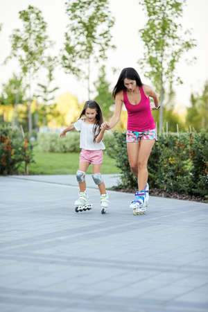 Young mother and her little daughter rollerskating in summer park Banco de Imagens