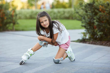 cute little child girl falled down while rollerskating in park. Banco de Imagens