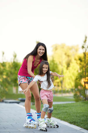 beautiful mother is teaching her little daughter to skate on roller skating in park. happy family