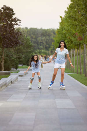 Young attractive mother and her little daughter rollerskating in summer park. happy family have fun Banco de Imagens - 155634005