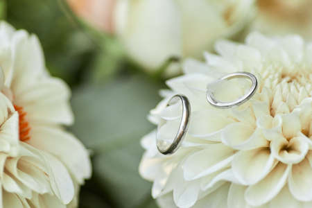 two wedding rings and beautiful flower bouquet, close-up Banco de Imagens - 155640910