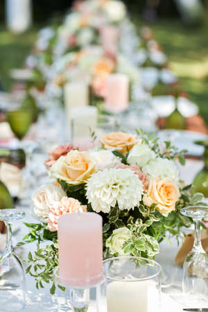 long dinner tables with white cloth, served with porcelains. Georgeous wedding table decorated with flowers and candles Banco de Imagens - 155875625