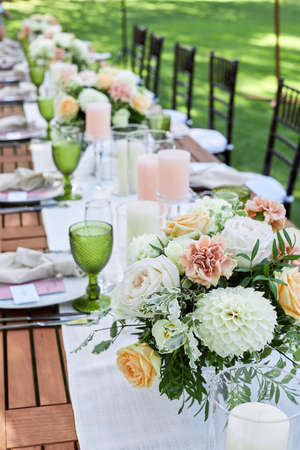dinner tables with white cloth, served with porcelain and green glasses. Georgeous wedding table decorated with flowers