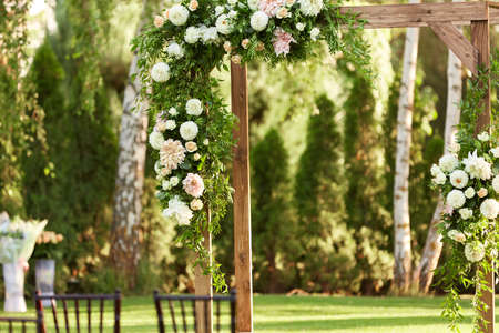 wooden arch for the wedding ceremony decorated with white flowers in sunny summer day Banco de Imagens