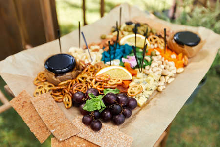 wooden buffet table with snack, appetizer and fruits decorated outdoor in summer day Banco de Imagens - 155848745
