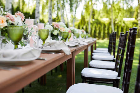 chairs and dinner tables with white cloth, served with porcelain and green glasses. Georgeous wedding table decorated with flowers on a green lawn Banco de Imagens - 155848775